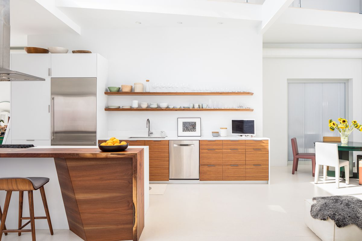 A white and timber kitchen has open shelving and a large kitchen island.