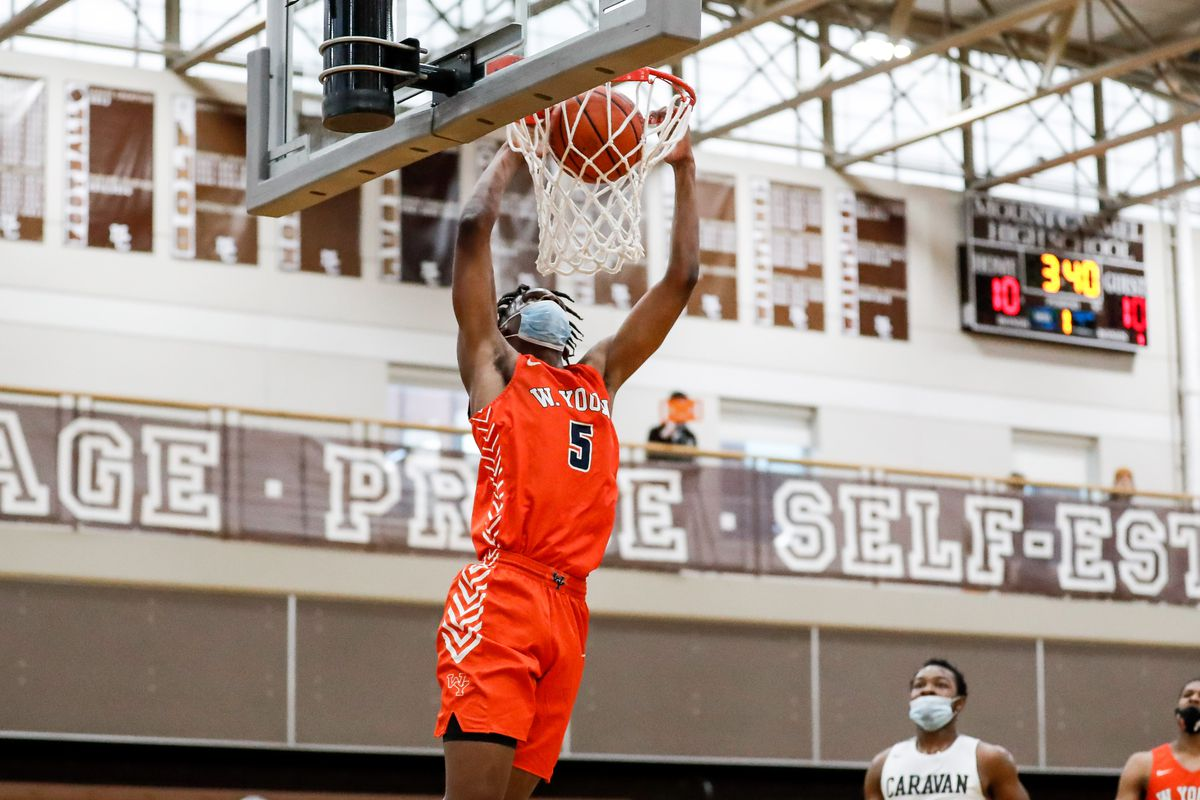 Young's Xavier Amos (5) dunks the ball over Mount Carmel.