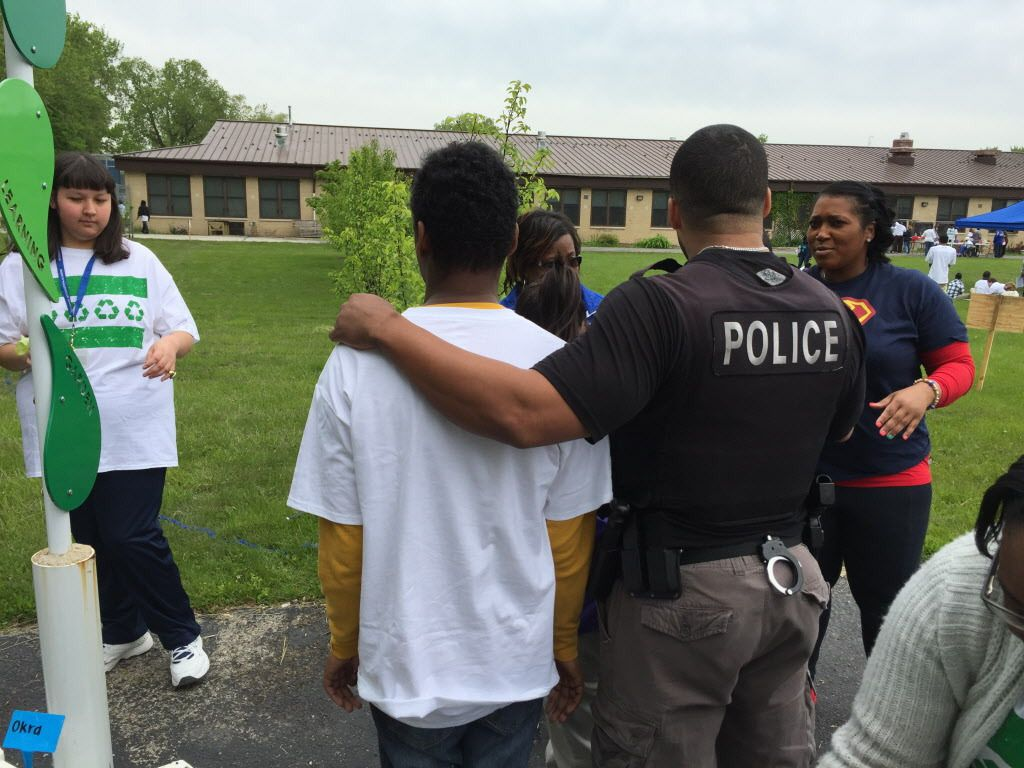 Chicago Police officer David Davis talks with a group of students at Southside Occupational Academy High School in Englewood while helping them plant a garden. | Neil Steinberg/Sun-Times
