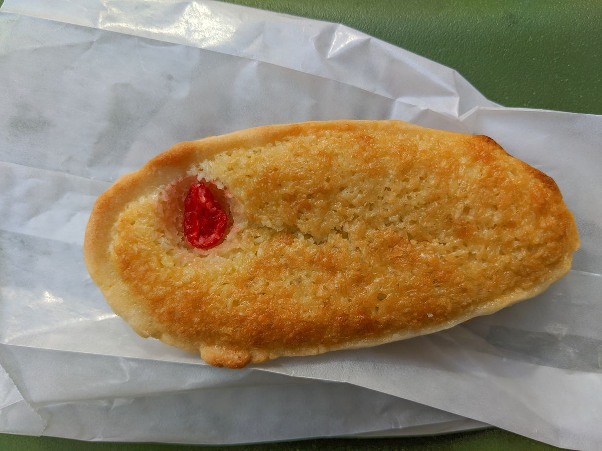 Overhead view of an oblong coconut tart with a maraschino cherry embedded in it, on a white paper bag on a green background