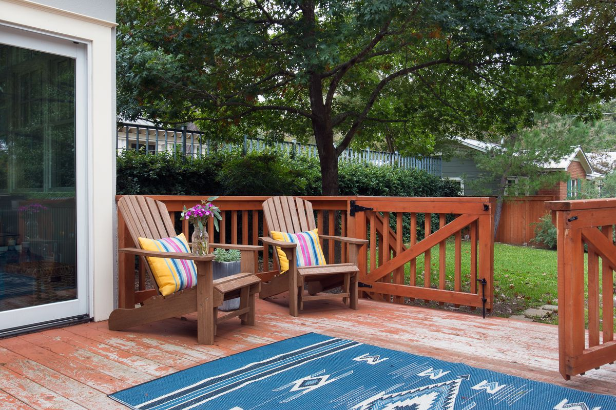 Photo of a small wooden deck and railing, kind of worn or broken in, with an open gate. There's an outdoor rug and two sort of Adirondack chairs. There's a mid-sized tree in back.