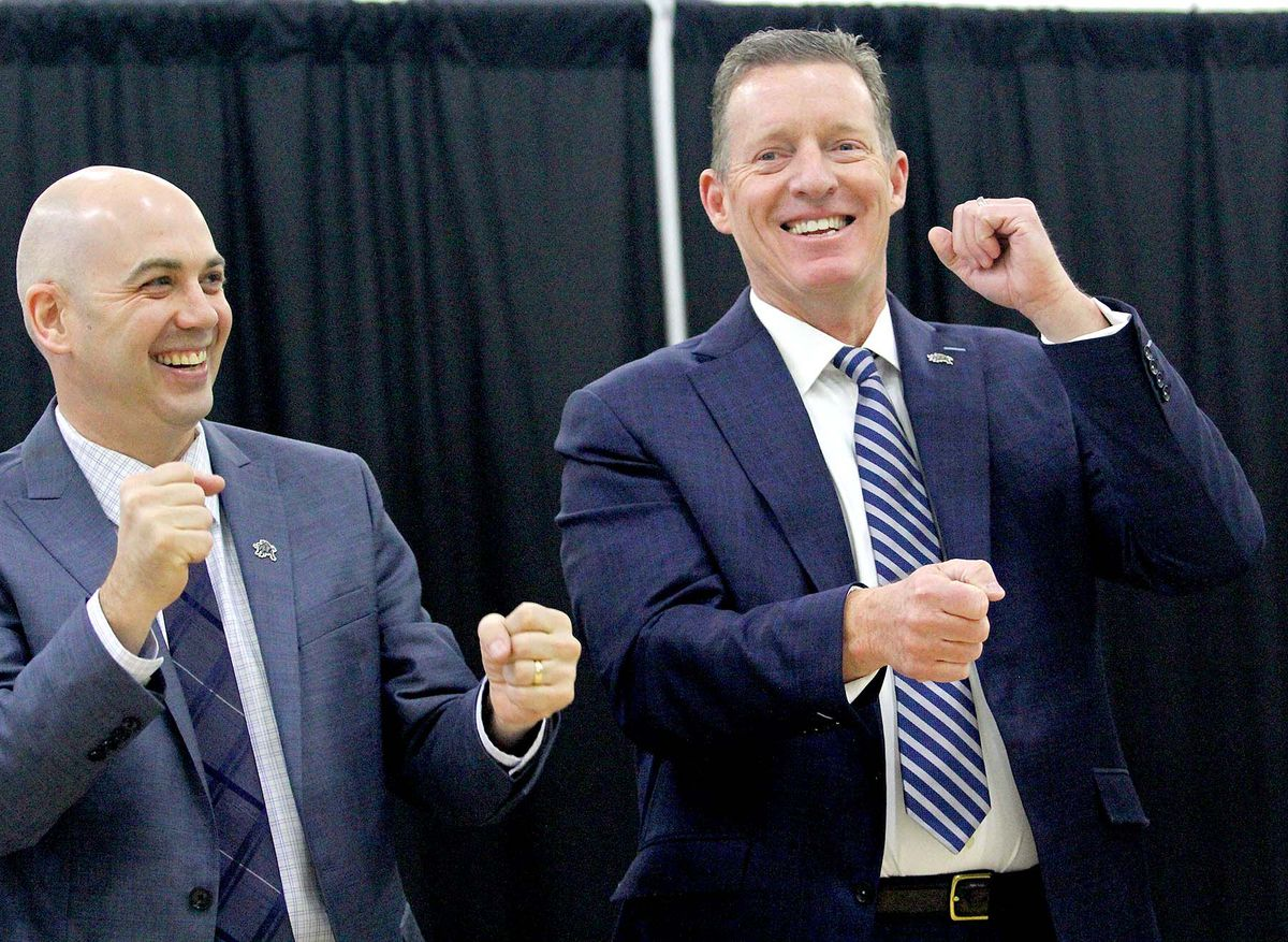 """Utah State head basketball coach Craig Smith, left, and USU athletic director perform """"The Scotsman"""" at the press conference announcing Smith's hiring on March 27, 2018."""