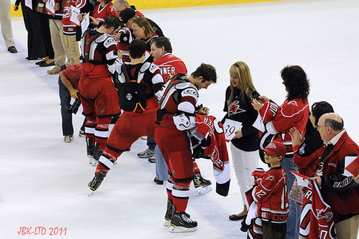 Carolina Hurricanes forwards Chad LaRose, Jeff Skinner, and Patrick Dwyer give the jerseys off their backs to fans after a game against the Tampa Bay Lightning on April 9, 2011 (author's photo).