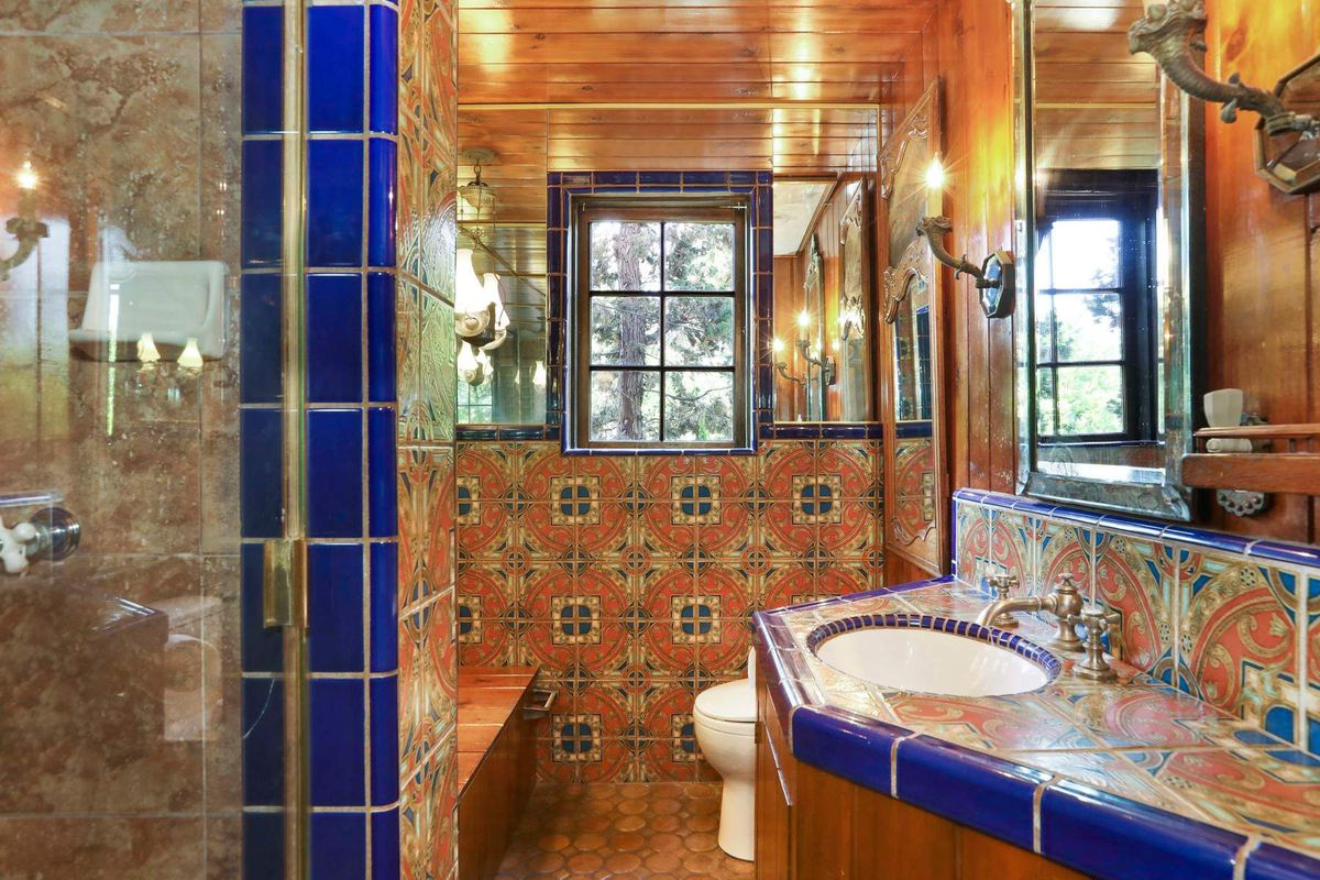 Bathroom featuring orange and blue tiles and a small window.