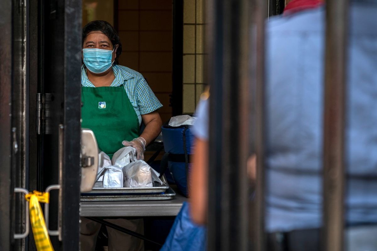A worker distributes grab-and-go lunch bags at Pace High School in Manhattan's Chinatown, Aug. 21, 2020.