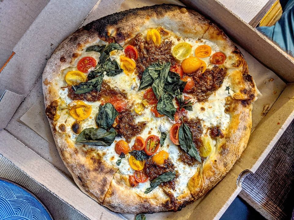 overhead view of a pizza in a takeout pizza box topped with fresh basil, cherry tomatoes, and a meaty jam