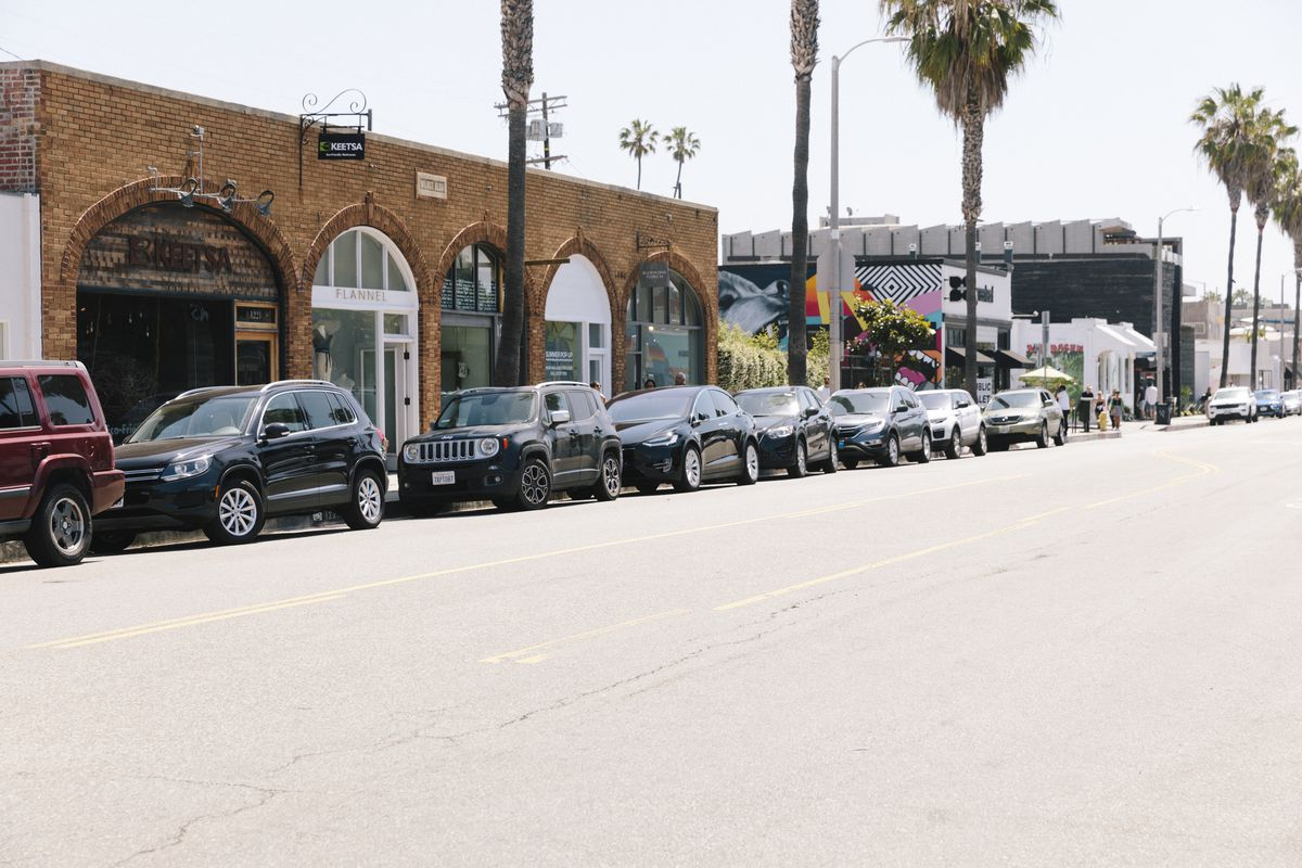 A line of cars parked in front of a brick building. In the background is a mural on a white building.