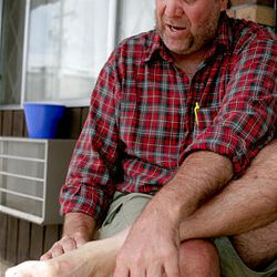 Backpacker Duane Lawson of Mesa, Ariz., inspects his feet on Aug. 4 outside his motel room in Roosevelt.