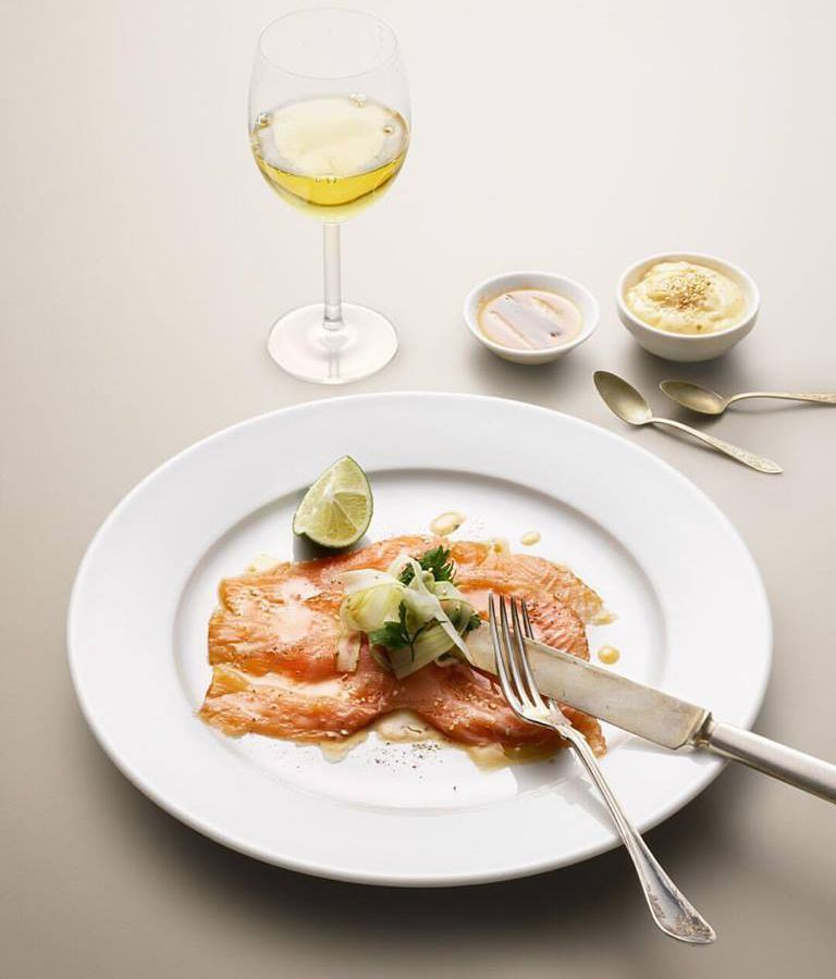 A fork and knife rest on top of sliced salmon gravlax beside a lime wedge, with a glass of wine and condiments nearby