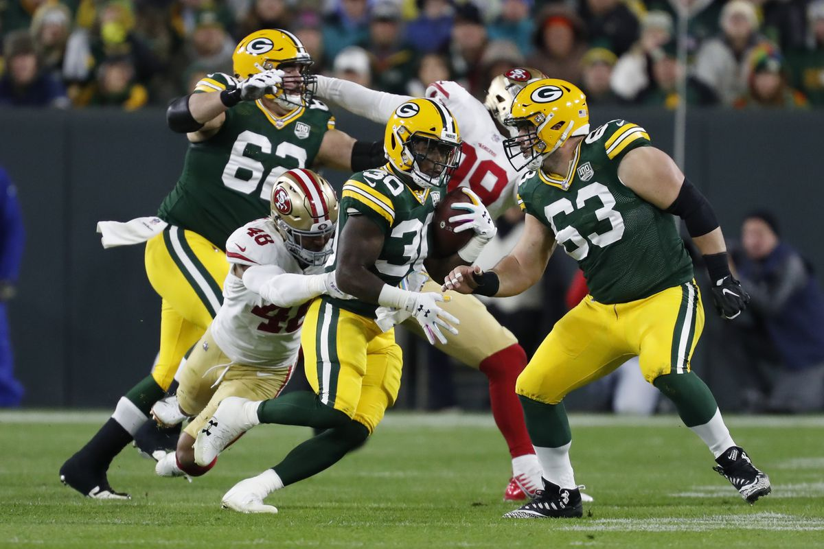 Green Bay Packers running back Jamaal Williams (30) runs against San Francisco 49ers defense, including linebacker Fred Warner (48), during the first half of an NFL football game Monday, Oct. 15, 2018, in Green Bay, Wis. Williams and Warner were teammates