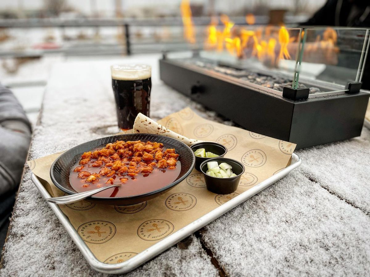 A bowl of soup with fixings and tortillas on a stone ledge by an outdoor fire pit and a glass of beer