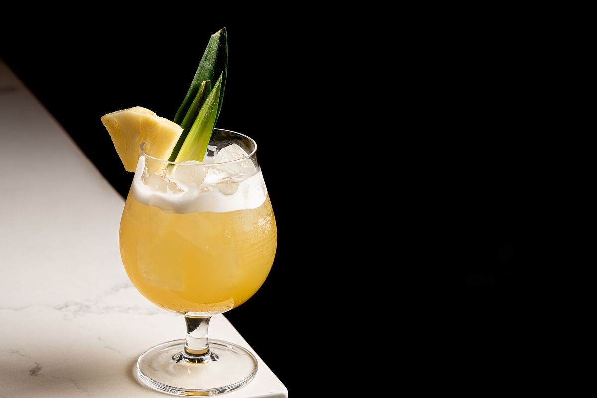 A yellow cocktail with pineapple in a coupe glass.