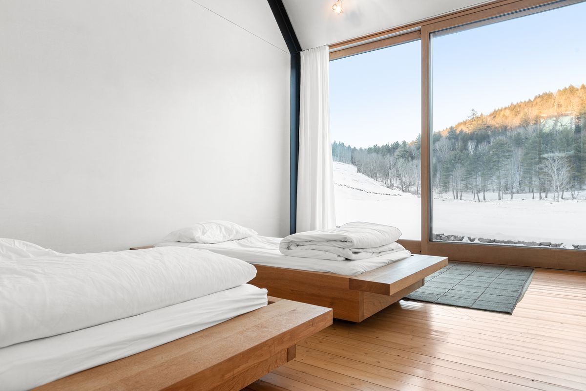 Two white platform beds look out onto a wall of windows with snow.