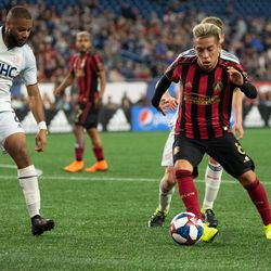 FOXBOROUGH, MA - APRIL 13: Atlanta United FC midfielder Ezequiel Barco #8 dribbles by two New England Revolution defenders during the first half at Gillette Stadium on April 13, 2019 in Foxborough, Massachusetts. (Photo by J. Alexander Dolan - The Bent Musket)