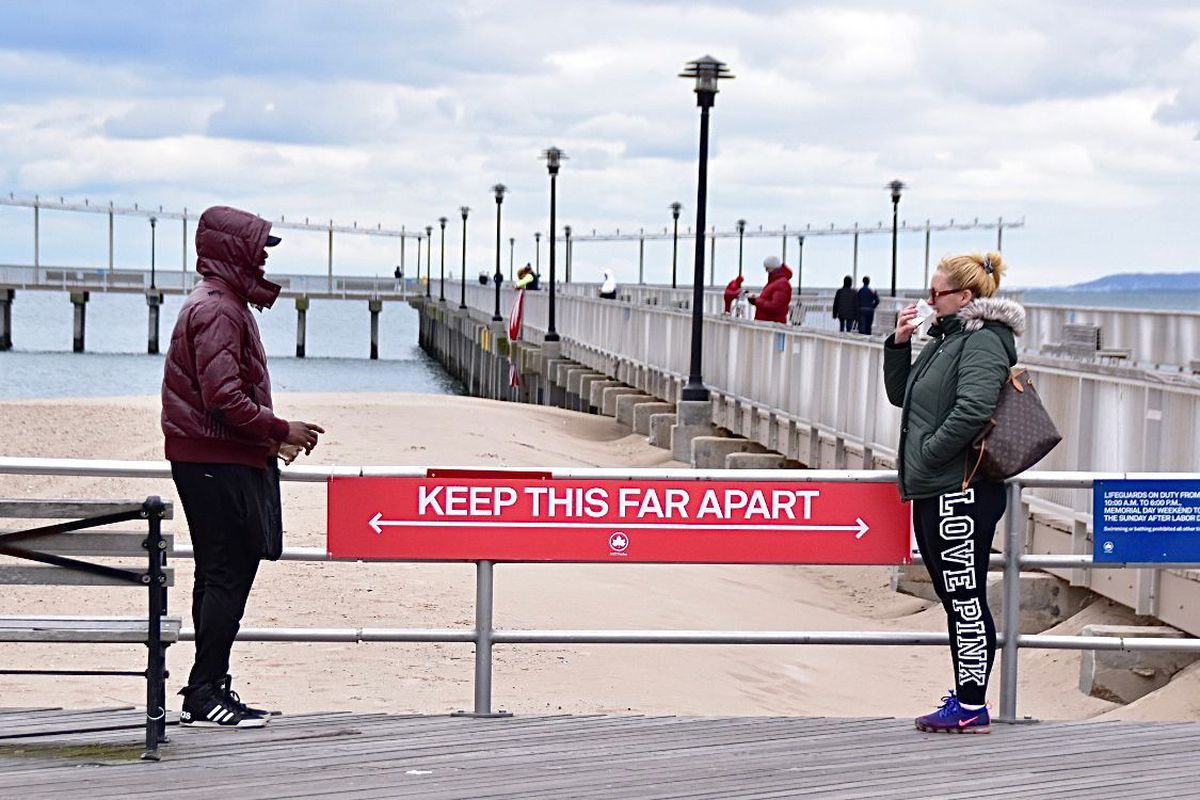 People talk to each other on the Coney Island Boardwalk in April while following social distancing guidelines.