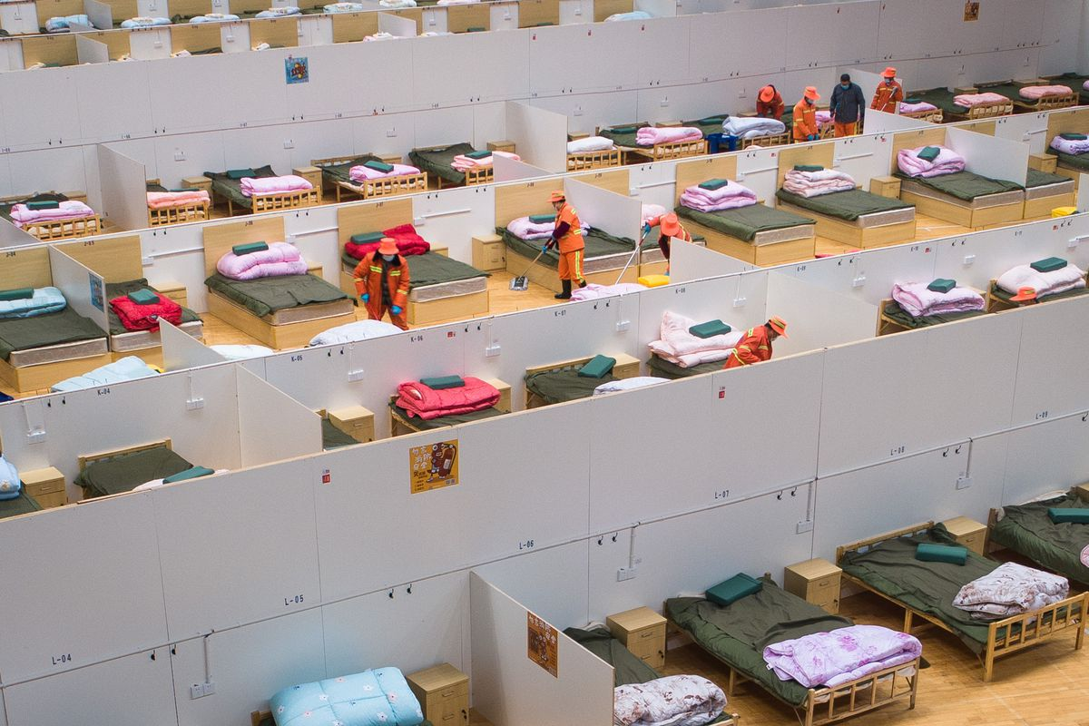Workers in a temporary hospital in Hubei province, China, clean around two of the dozens of beds visible in the photograph.