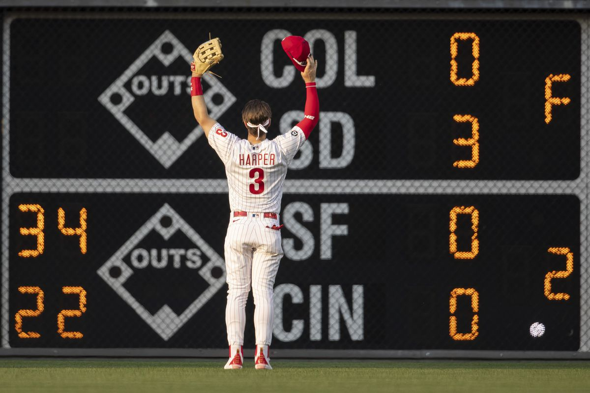 bryce harper signals to fans at the stadium in the field