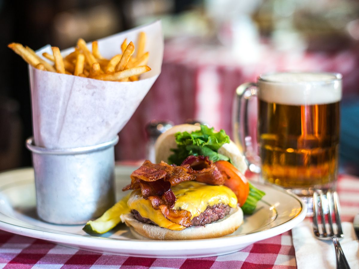 An open-faced burger with lettuce, tomato, onion, and cheese next to a side of fries