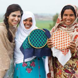 Two embroidery artisans show off their work and pose with Saba Gul, Popinjay founder.
