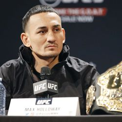 Max Holloway listens to a question during presser.