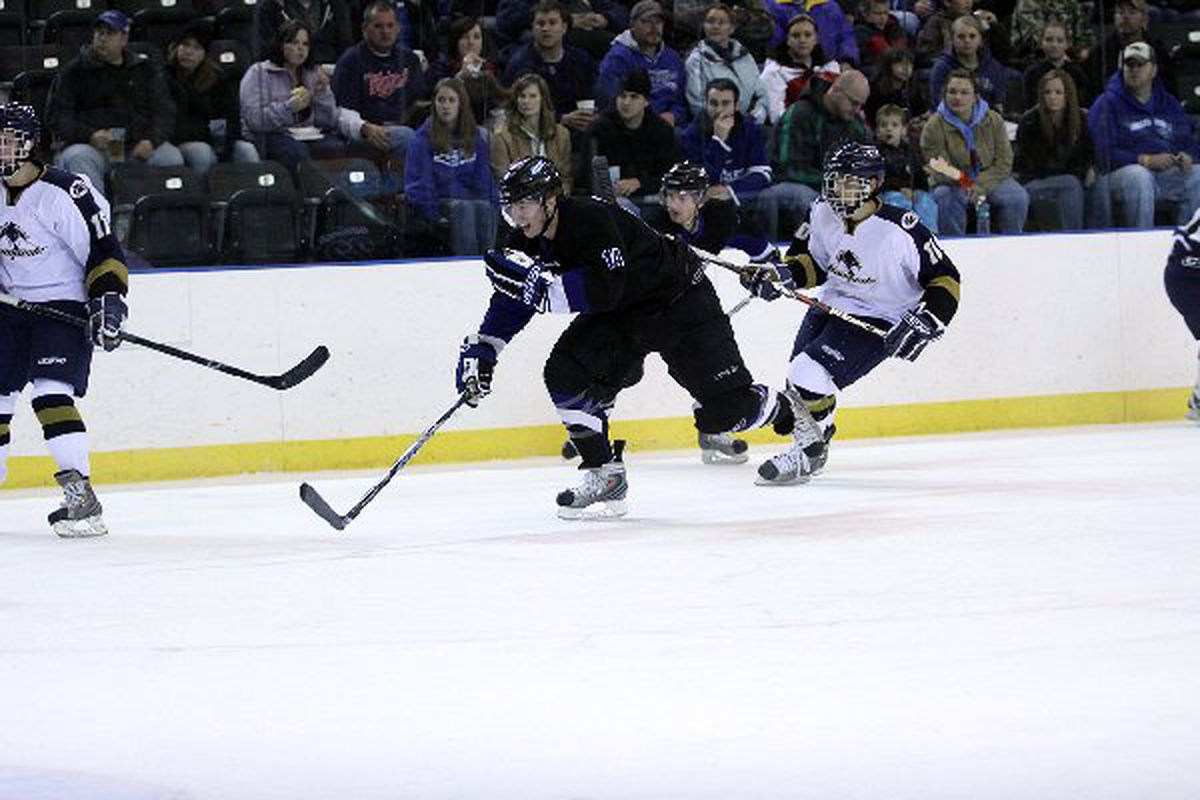 """Nick Oliver (#14 in black) has a reputation as a hard-working forward who uses his 6'3"""" frame to his advantage. Image via <a href=""""http://www.fargoforce.com/images/gallery/large/676_img_7030.jpg"""">www.fargoforce.com</a>"""