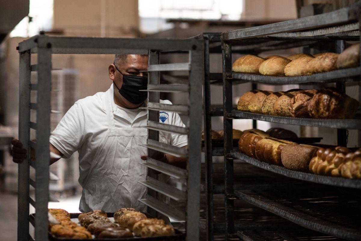 Một nhân viên đeo khẩu trang di chuyển quanh các khay bánh nướng để giải nhiệt.