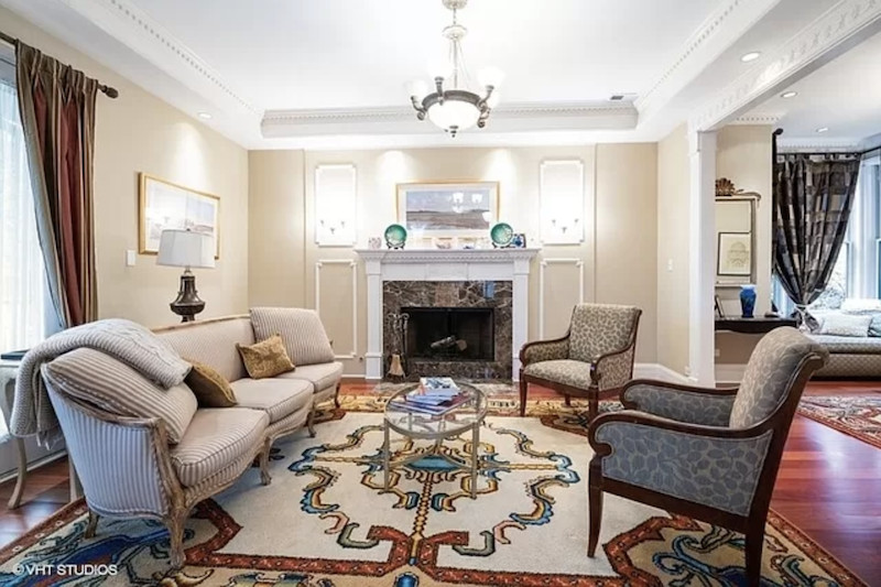 An ornate living room with a pattern carpet, footed couch and chairs. and a stone fireplace.