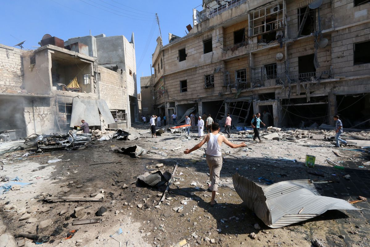 ALEPPO, SYRIA - AUGUST 13. Syrians gather at the site of a reported barrel-bomb attack by government forces