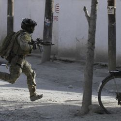 A NATO soldier runs to the scene of an attack in Kabul, Afghanistan, Sunday, April 15, 2012. The Taliban launched a series of coordinated attacks on at least seven sites across the Afghan capital on Sunday, targeting NATO headquarters, the parliament and diplomatic residences. Militants also launched near-simultaneous assaults in three other eastern cities. (AP Photo/Ahmad Jamshid)
