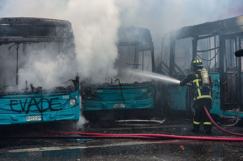 A firefighter hoses down burning buses.
