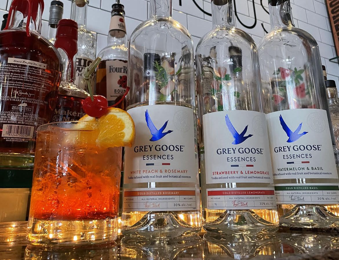Three Grey Goose Essences liquor bottles in front of a subway tile bar wall that says Detroit Fish House, next to an orange colored cocktail topped with an orange slice and a cherry