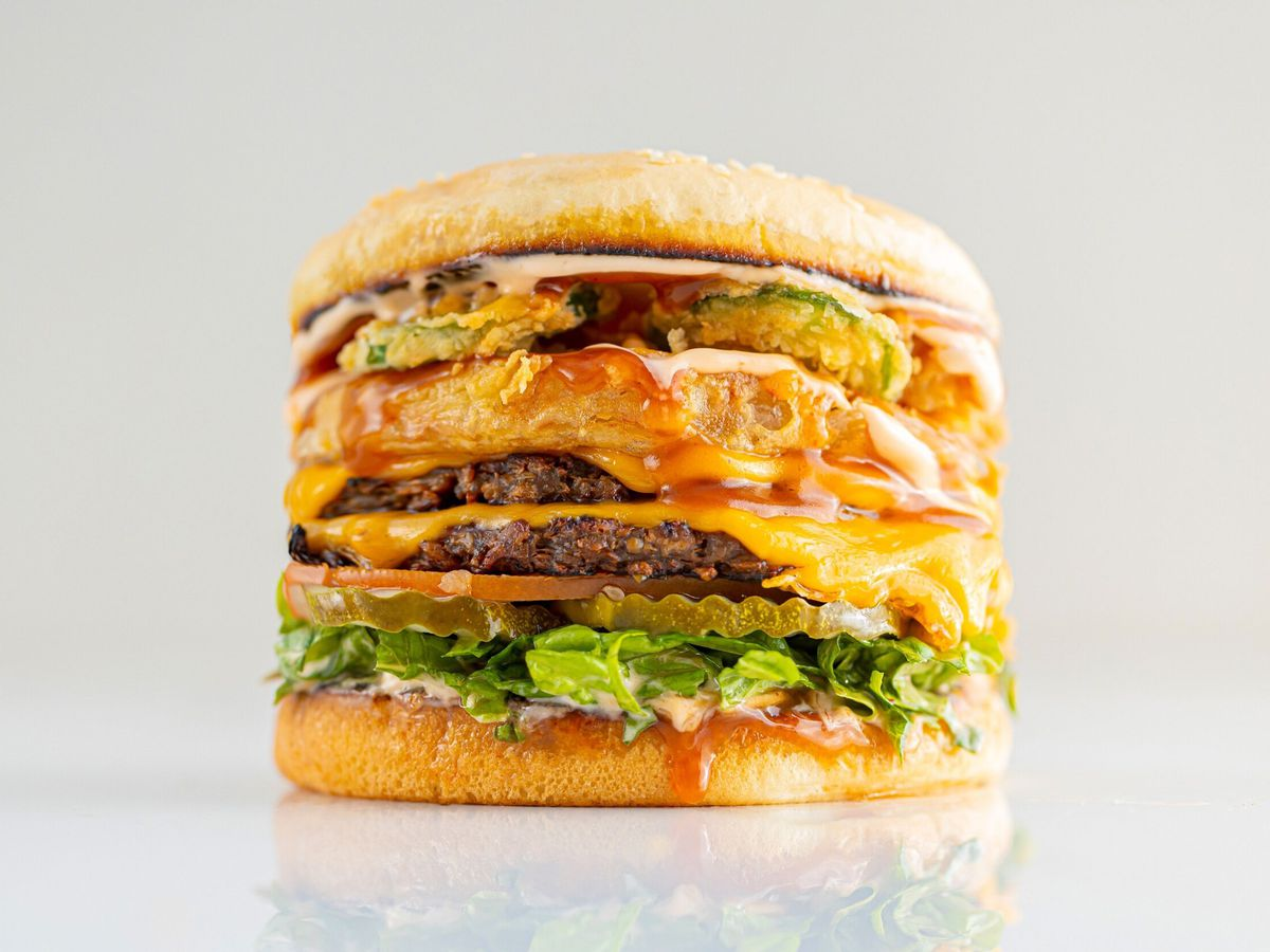 A stacked burger with fried ingredients and melty cheese on a white background.