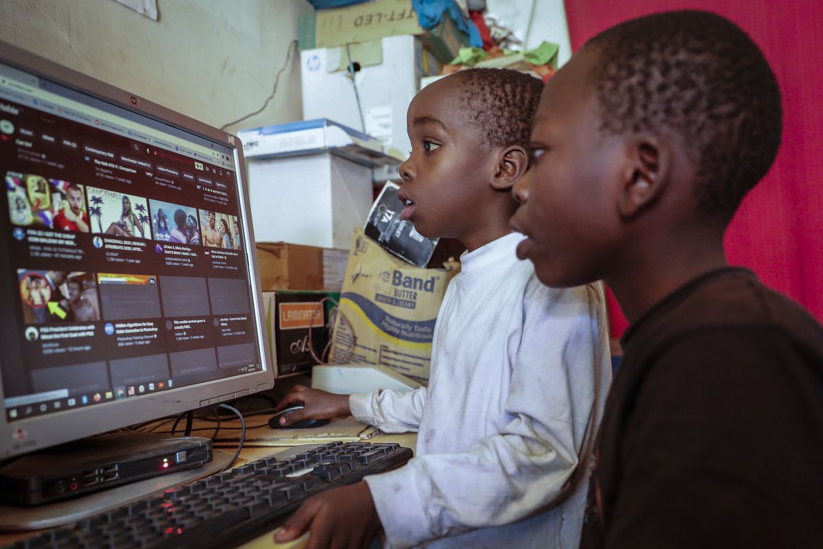 Two young boys use a computer at an Internet cafe in the low-income Kibera neighborhood of Nairobi, Kenya.
