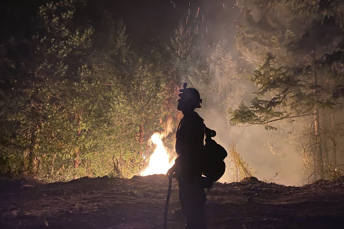 This photo provided by the Unified Fire Authority shows a Utah fire crew member on the scene working to protect the town of Butte Falls in southern Oregon on Sunday, Sept. 13. 2020.