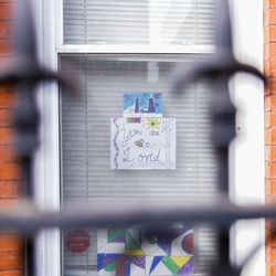 """A sign that reads """"you are loved"""" hangs in the window of a home in the East Village neighborhood, Monday, April 6, 2020."""