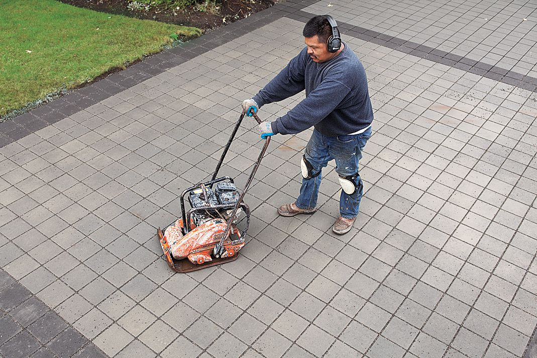 Man Runs Plate Compactor Over Driveway
