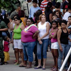 Residents of a building wait outside it as police officers allegedly look for the abductors of Costa Rican diplomat Guillermo Cholele in Caracas, Venezuela, Monday April 9, 2012. Cholele was kidnapped on Sunday in Venezuela and his abductors have demanded a ransom, Costa Rican officials said Monday.