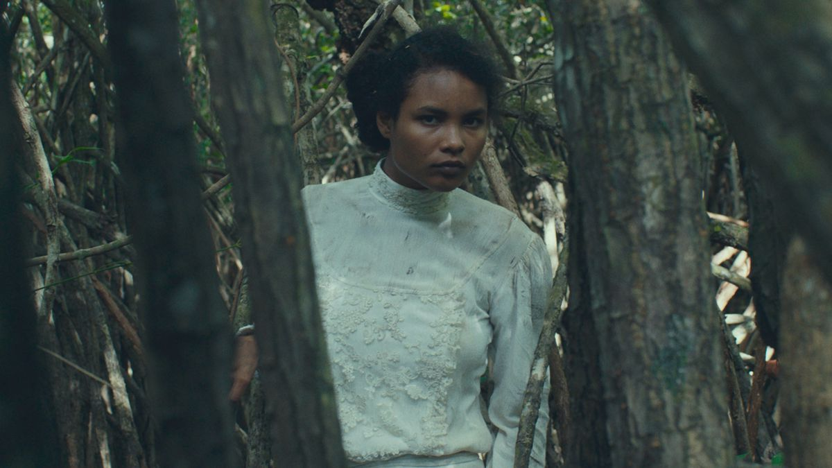 A woman in white, played by Indira Rubie Andrewin, peers between trees in Tragic Jungle