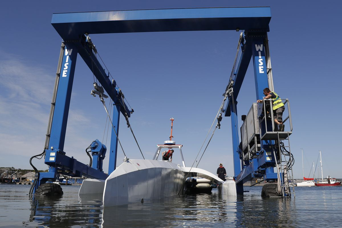 Technicians lower the Mayflower Autonomous Ship into the water at its launch site for its first outing on water since being built in Turnchapel, Plymouth in southwest England. The robot ship on Tuesday began a trans-Atlantic crossing that could take up to three weeks.