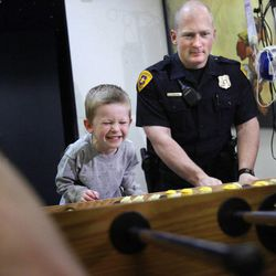 Parker Evans,4, of Holladay, plays foosball with Salt Lake police officer Josh Ashdown at Primary Children's Medical Center in Salt Lake City on Thursday, Jan. 19, 2012.  Parker's older brother is a patient in the hospital and is not allowed to leave his room. The playroom is a good place for Parker to play and blow off steam after visiting his brother.
