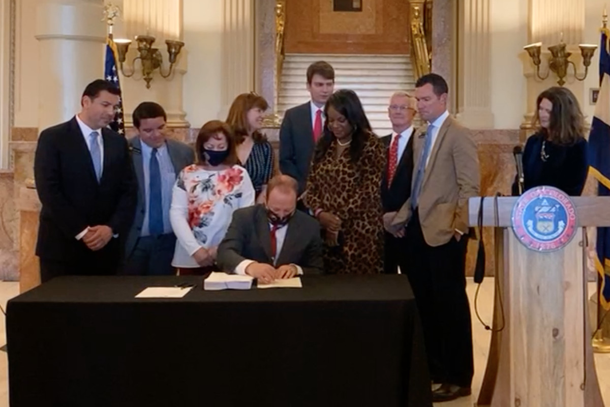 Seated at a table covered by a dark cloth, Gov. Jared Polis signs a piece of paper next to a large stack of documents. Colorado legislators stand around him looking on.