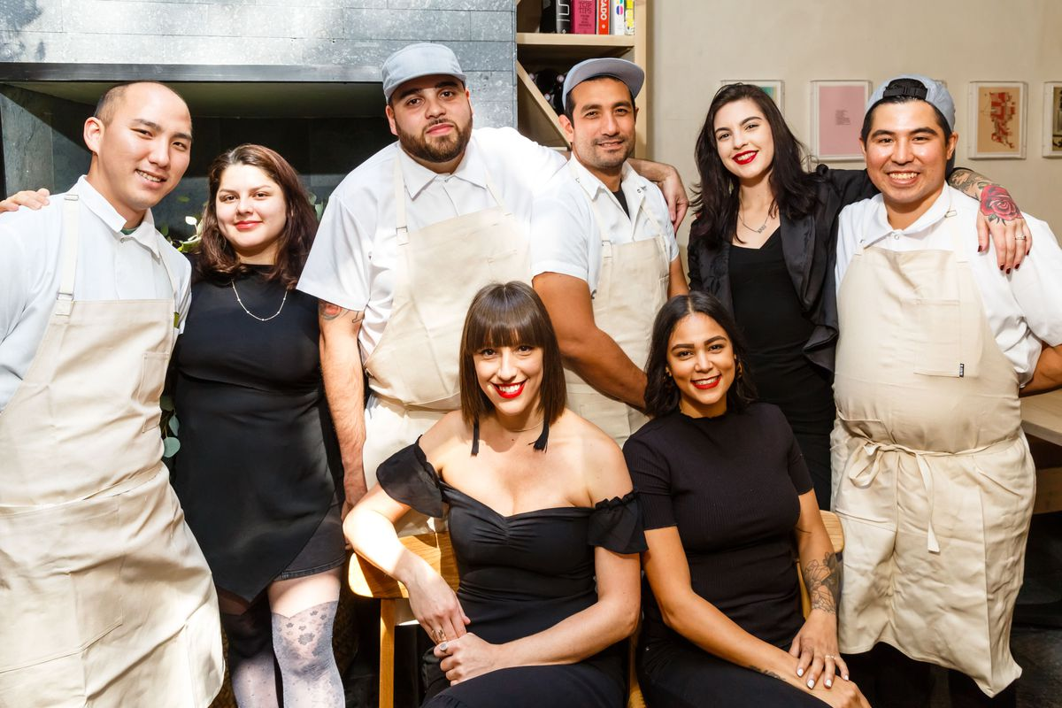 A smiling group of women dressed in black and men wearing white chef coats