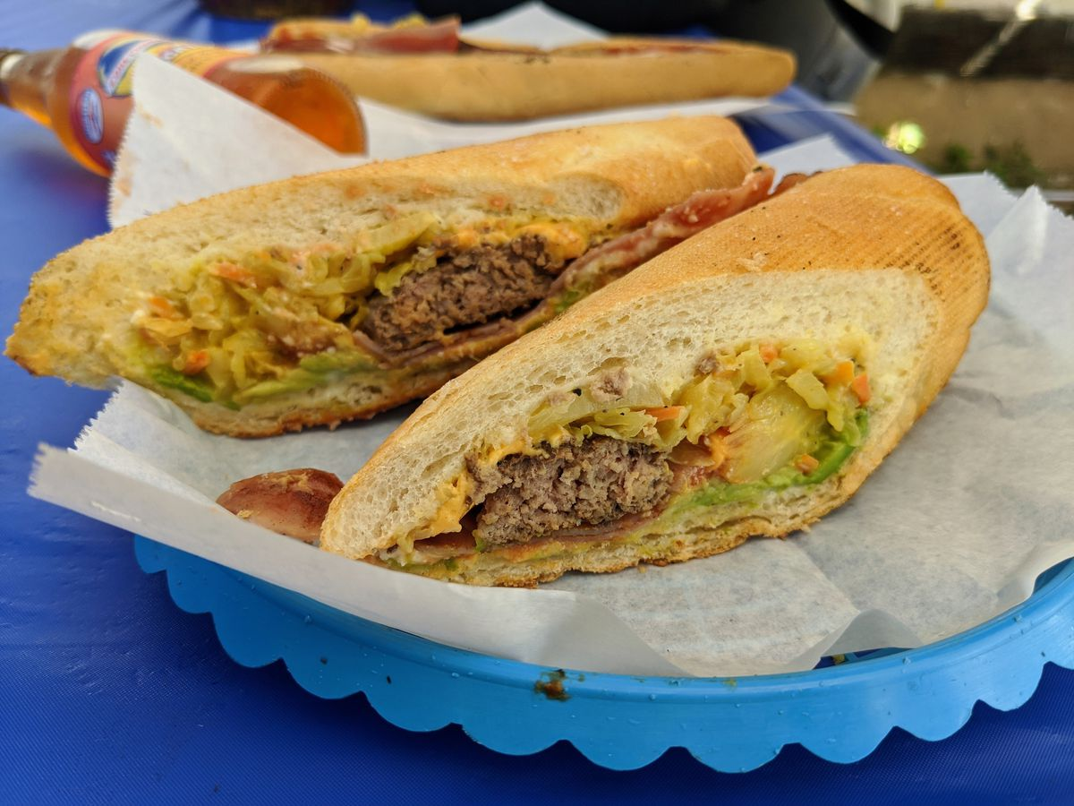 A sandwich filled with a hamburger patty, cheese, and avodcado.