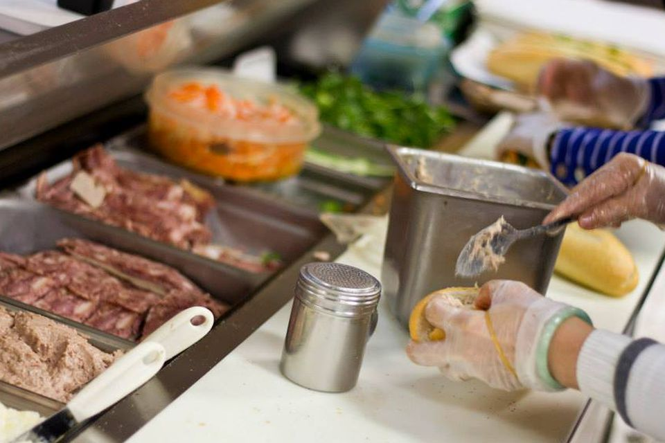 A station of cold cuts and condiments with a worker slathering on dressing