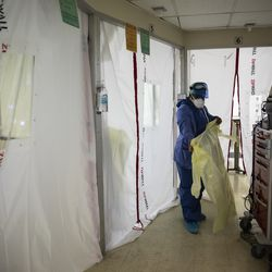 Nurse Tamara Jones puts on new personal protective equipment as she prepares to checks on a patient with COVID-19 in the Intensive Care Unit at Roseland Community Hospital on the Far South Side, Tuesday afternoon, Dec. 8, 2020. Zip walls and negative pressure machines were installed in the hospital's ICU in early December.