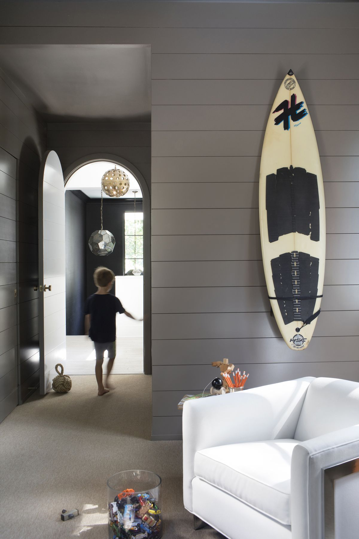 A surf board hangs on the wall of the son's bedroom.