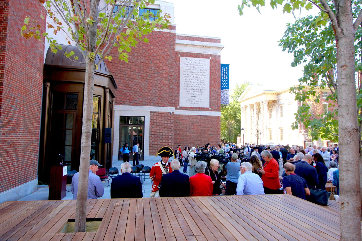 The view of the public plaza at the Museum of the American Revolution, filled with hundreds of people, some sitting on a stadium-style wood-paneled bench.