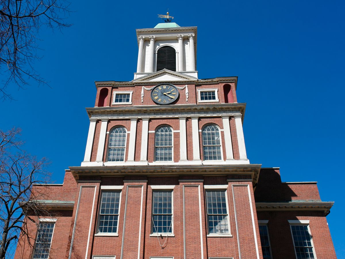 A tall, kind of wedding-cake-like brick building ending in a thin steeple on top.