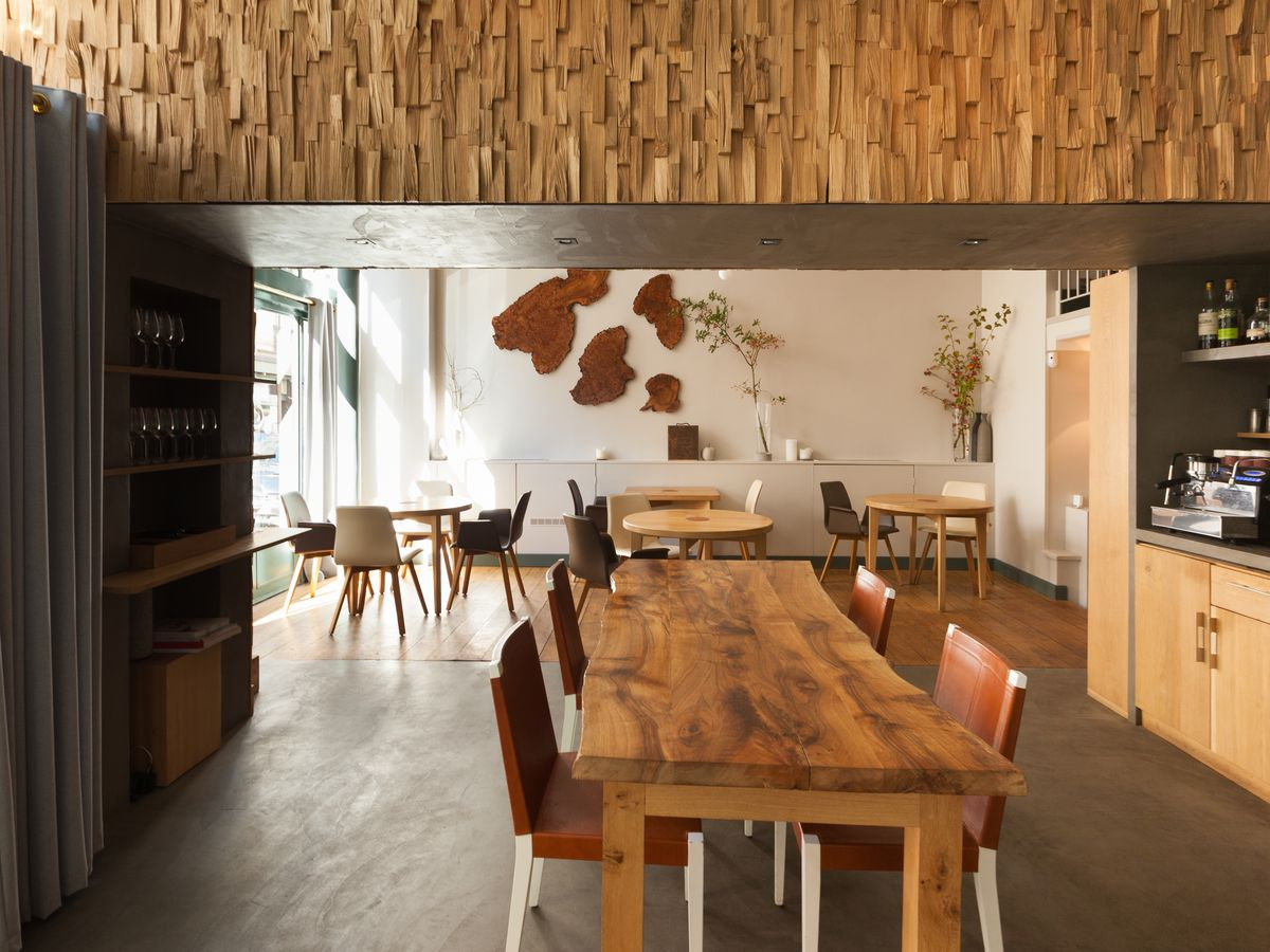 A casual dining room with lots of exposed wood floors and walls, long farmhouse tables with simple chairs, and large windows for natural light