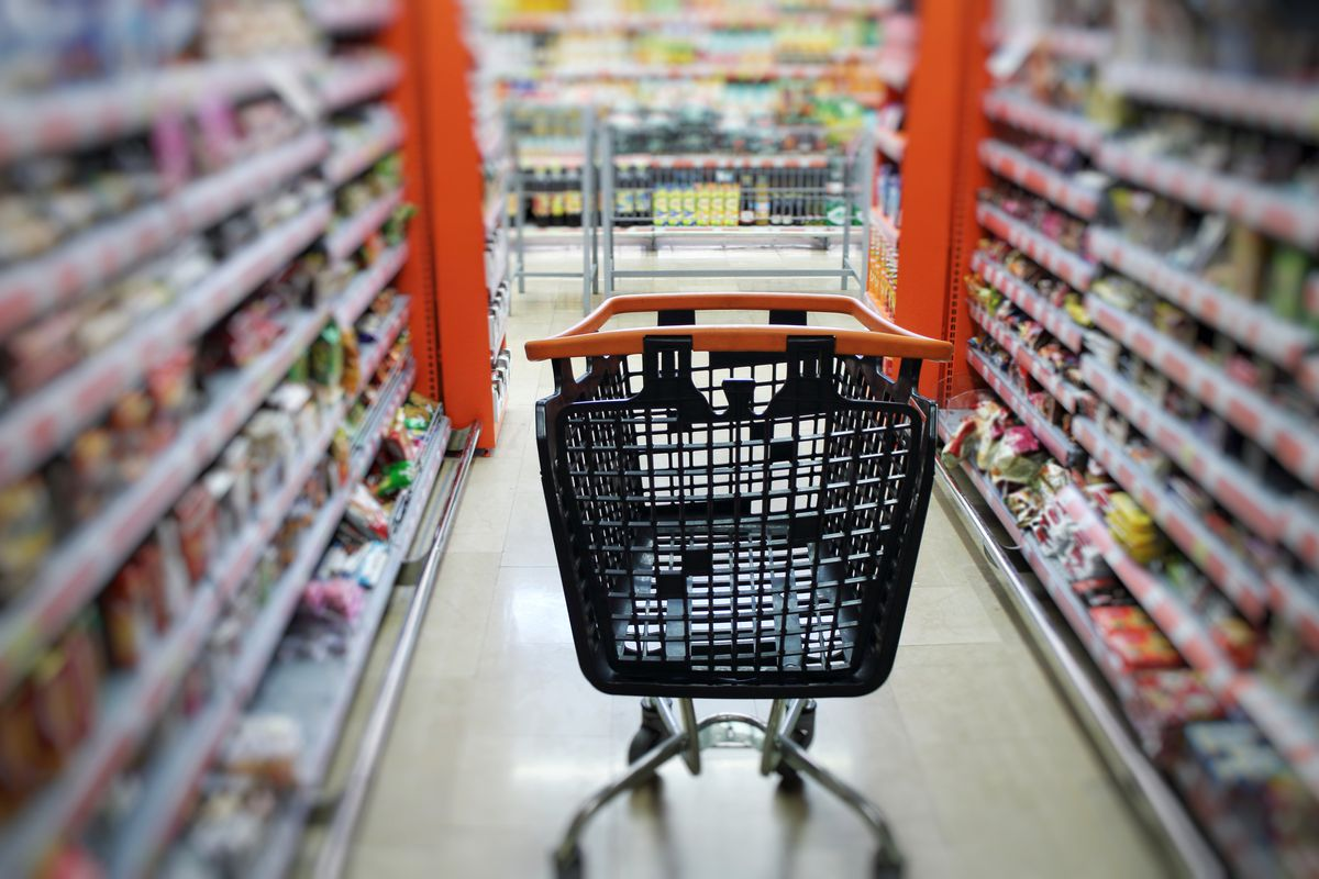 An empty cart in a grocery store aisle.